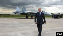 PM Rusia Vladimir Putin dengan latar belakang pesawat siluman andalan terbaru Rusia, Sukhoi T-50 (16/8)