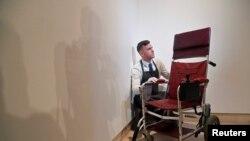 Tom Richardson, salah seorang yang bertanggung jawab menangani barang-barang lelang bercita rasa tinggi tampak berpose dengan kursi roda bermotor milik fisikawan Inggris, Stephen Hawking sebelum pelaksanaan lelang barang-barang pribadi milik Hawking di Balai Lelang Christie di London, Inggris, 30 Oktober 2018 (foto: Reuters/Toby Melville)