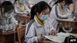Учні школи у китайському місті Ухань сидять у класі за прозорими перегородками. 6 травня 2020 р.
