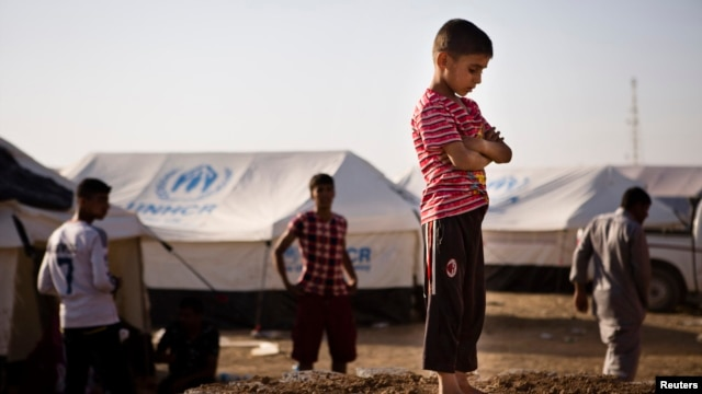 A boy, who fled from the violence in Mosul, stands near tents in a camp for internally displaced people on the outskirts of Erbil in Iraq's Kurdistan region, June 14, 2014.