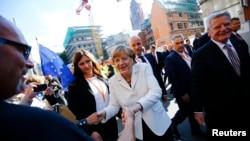 Канцлер Ангела Меркель (в центре) и президент Йоаким Гаук (справа) на улице Франкфурта, Германия. 3 октября 2015 г.