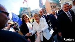 10月3日,德國總理默克爾(中)和總統高克(右)在法蘭克福街頭與民眾慶祝國家統一25週年。
