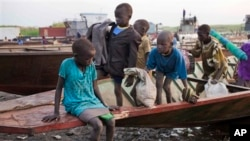 A group of displaced brothers and sisters cautiously disembark from a boat that has just carried them across the Nile to a village in Awerial, which has received tens of thousands of displaced people who crossed the Nile river by boat to flee the recent f