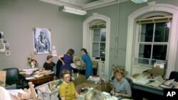 Nancy Tuckerman (teal dress) and volunteers help answer condolence and Christmas mail, Executive Office Building, 11 December 1963.