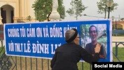 Thân mẫu nhà hoạt động Lê Đình Lượng chạm vào hình con mình trên một banner treo phía trước nhà thờ gần tòa án Vinh, 18 tháng 10, 2018. (Facebook Nguyen Xoan)