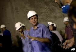 FILE - Rio de Janeiro's Mayor Eduardo Paes, center, talks with the media inside the Expressway Tunnel in Rio de Janeiro, Brazil, March 24, 2015.