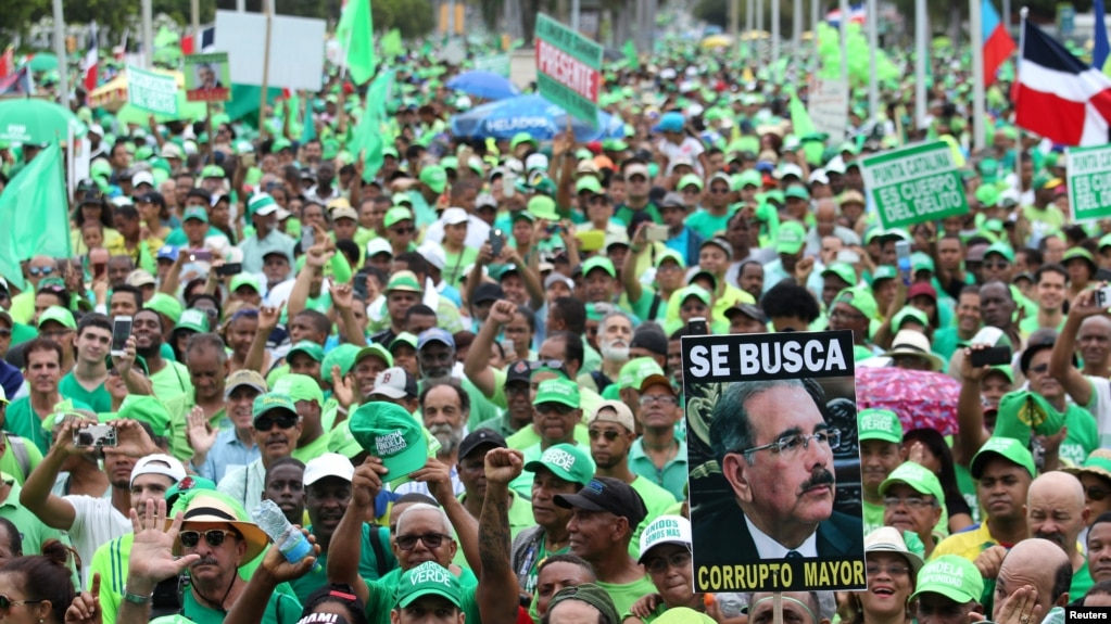 """People march during a protest against corruption and the Brazilian conglomerate Odebrecht SA, in Santo Domingo, Dominican Republic, July 16, 2017. The sign reads """"Wanted corrupt senior."""""""