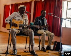Zimbabwe music icon Oliver 'Tuku' Mtukudzi (L) plays his guitar during a rehearsal with a group of young musicians who are incubated at his Pakare Paye Arts and Music Centre in Norton 45km from the country's capital city Harare on January 12, 2018