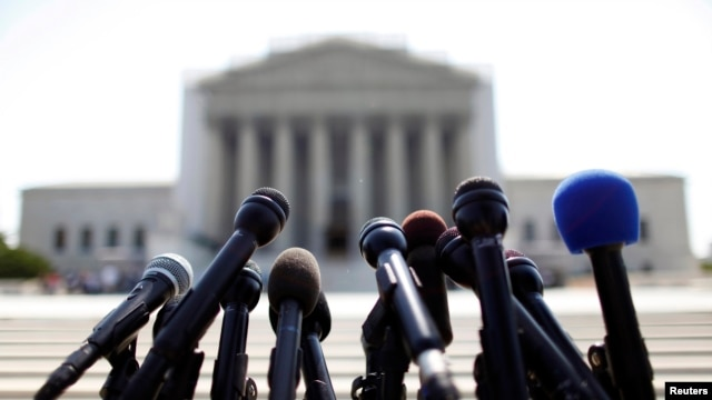 FILE - News microphones wait to capture reactions from US Supreme Court rulings outside the court building in Washington.