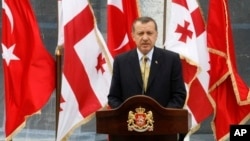 With Georgian and Turkish flags in the background, Turkish Prime Minister Recep Tayyip Erdogan speaks at a news conference in Tbilisi, Georgia, Aug. 14. 2008.