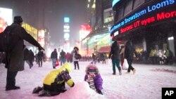 Anak-anak bermain salju di Times Square, New York (2/1).