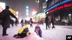 Unos niños hacen una montaña de nieve en Times Square, Nueva York, durante la tormenta de nieve.