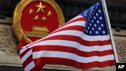 FILE - In this Nov. 9, 2017, file photo, an American flag is flown next to the Chinese national emblem during a welcome ceremony for visiting U.S. China says accusations against an alleged spy of attempting to steal trade secrets from several American avi