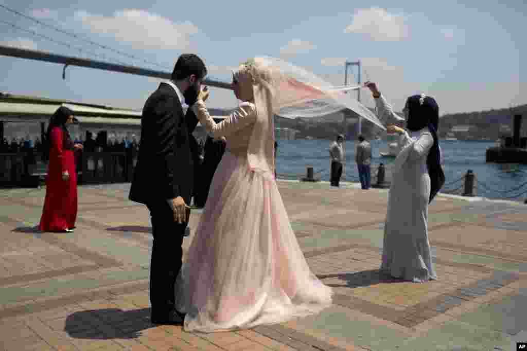 Pasangan pengantin baru berfoto di depan jembatan Bosporous di Istanbul, Turki pasca aksi kudeta yang gagal.