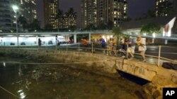 Du khách và cư dân Oahu đứng xem mực nước tại cảng Ala Wai, ngày 27/10/2012