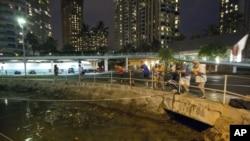 星期六在檀香山瓦胡島的遊客和居民注視著阿拉威港的水位。他們等待海嘯的到來。