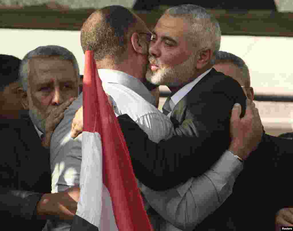 Senior Hamas leader Ismail Haniyeh hugs the brother of Hamas military chief Ahmed Jaabari, who was killed by an Israeli air strike, during a rally in Gaza City November 22