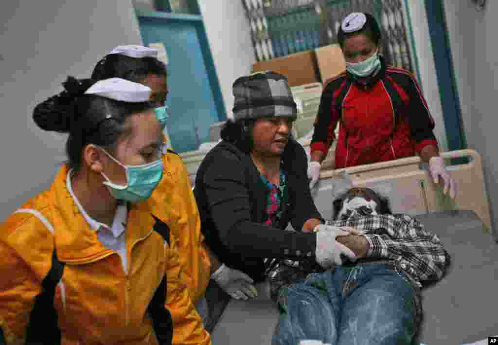 Nurses dress a victim of the eruption of Mount Sinabung for burial at a hospital in Kabanjahe, North Sumatra, Indonesia, Feb. 1, 2014.