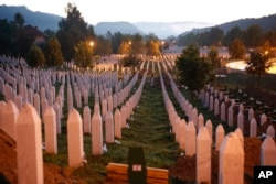 FILE - Gravestones are seen at sunrise at a memorial complex near Srebrenica, 150 kilometers (94 miles) northeast of Sarajevo, Bosnia-Herzegovina, July 11, 2015. Twenty years earlier, Serb troops overran the eastern Bosnian Muslim enclave of Srebrenica and executed 8,000 Muslim men and boys, which International courts have labeled as an act of genocide.
