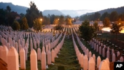 FILE - Gravestones are seen at sunrise at a memorial complex near Srebrenica, 150 kilometers (94 miles) northeast of Sarajevo, Bosnia and Herzegovina, July 11, 2015.
