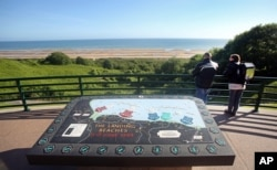 Two visitors look out over Omaha Beach from the Colleville American military cemetery in Colleville-sur-Mer, western France, June 6, 2015.