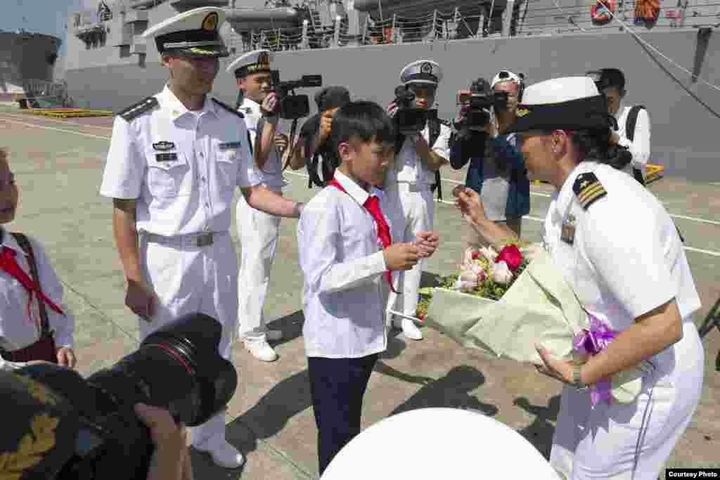 美軍斯泰雷特號導彈驅逐艦2017年6月12日抵達中國湛江港時女艦長卡洛里從中國少年手裡接過鮮花後,展示該軍艦的紀念性硬幣(美國海軍照片)。這是川普行政當局年初上任以來兩國海軍之間首次進行艦艇互訪,這標誌著美中兩國恢復了擱置幾個月之久的海軍互訪項目。