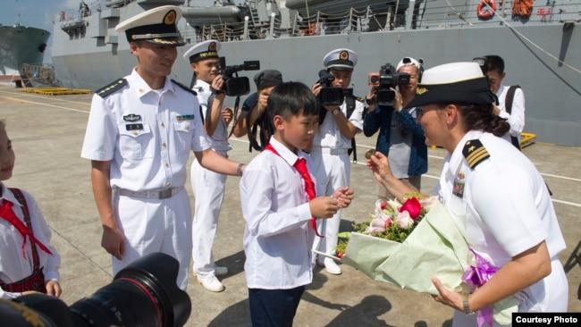 美軍斯泰雷特號導彈驅逐艦2017年6月12日抵達中國湛江港時女艦長接過鮮花(美國海軍照片)