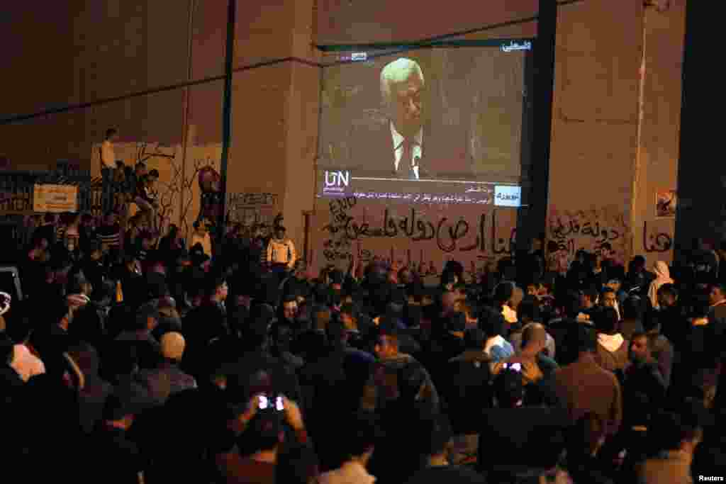 Palestinians rally while Palestinian President Mahmoud Abbas's speech is projected on Israel's controversial barrier in the occupied West Bank city of Bethlehem, November 29, 2012.