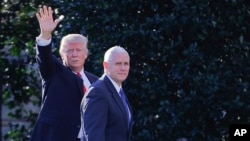 FILE - President Donald Trump, left, accompanied by Vice President Mike Pence, waves to members of the media as they walk to the Oval Office of the White House in Washington, Jan. 25, 2017