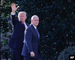 FILE - President Donald Trump, accompanied by Vice President Mike Pence, left, waves to members of the media as they walk to the Oval Office of the White House in Washington, Jan. 25, 2017.