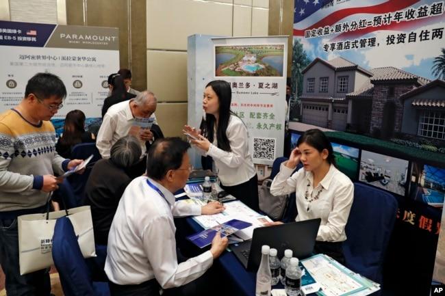 在妮可·库什纳(Nicole Kushner Meyer现身北京的一场投资移民项目(EB-5)推介会的一天之后,在投资美国展览中,在EB-5签证项目摊位上,中国人询问信息(2017年5月7日)