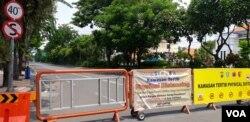 Jalan Raya Darmo saat ditutup dalam upaya mengurangi mobilitas masyarakat di jalan (foto: VOA/Petrus).