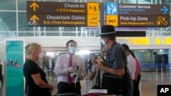 Petugas bandara memeriksa warga Australia setibanya di bandara internasional Ngurah Rai, Bali, 18 Agustus 2021. (AP Photo/Firdia Lisnawati)