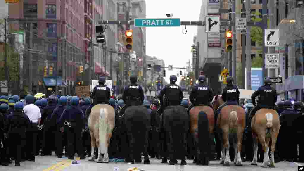 Polisi berusaha menghalangi demonstran yang memblokir jalan Pratt setelah berbaris menuju balai kota untuk Freddie Gray di Baltimore (25/4). (AP/Alex Brandon)