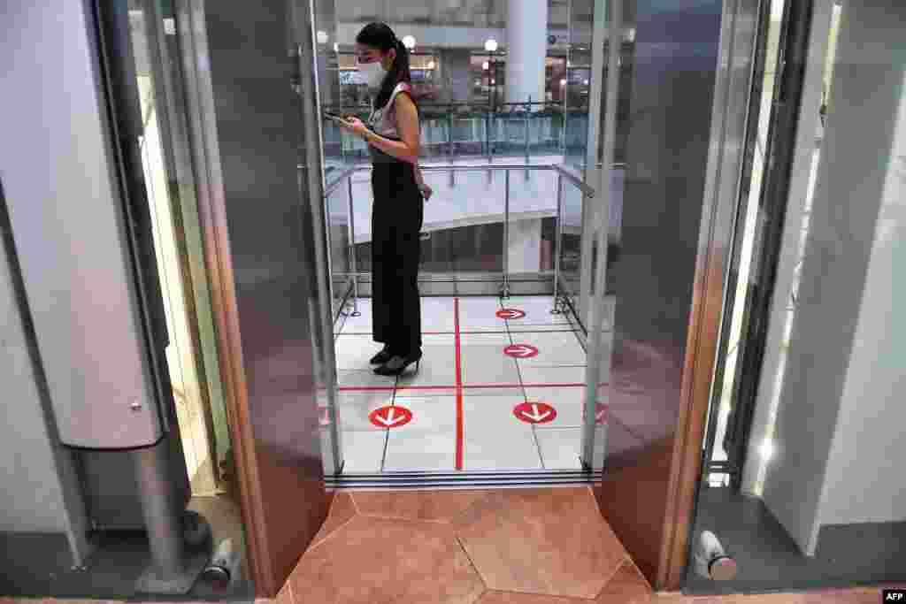 Mjini Bangkok, Thailand mwanamke anasimama ndani ya lifti katika mahala iliyowekwa alama watu kutokaribiana katika jengo la maduka ili kupambana na COVID-19.