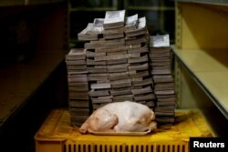 Karakas marketində 2,4 kiloqramlıq toyuq 14,600,000 bolivarın ($2,22) qarşısında çəkilib, Venesuela, 16 avqust, 2018-ci il.