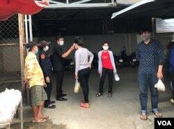 សន្តិសុខកម្មកររោងចក្រកាត់ដេរប្រភឹសឹស ខេមបូឌា ហ្គាមេន អិលធីឌី ក្នុងខេត្តកណ្តាល ត្រួតពិនិត្យកម្តៅកម្មករនៅពេលចូលរោងចក្រ នាថ្ងៃទី២០ ខែមីនា ឆ្នាំ២០២០។ (កាន់ វិច្ឆិកា/VOA Khmer)