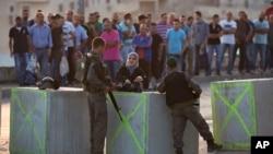Polisi Israel memeriksa kartu identitas warga Palestina saat mereka keluar dari distrik Issawiyeh yang merupakan kediaman warga etnis Arab di Yerusalem, Minggu (18/10)/
