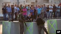 以色列边界警察正在检查从耶路撒冷阿拉伯社区出来的巴勒斯坦人的身份证件。