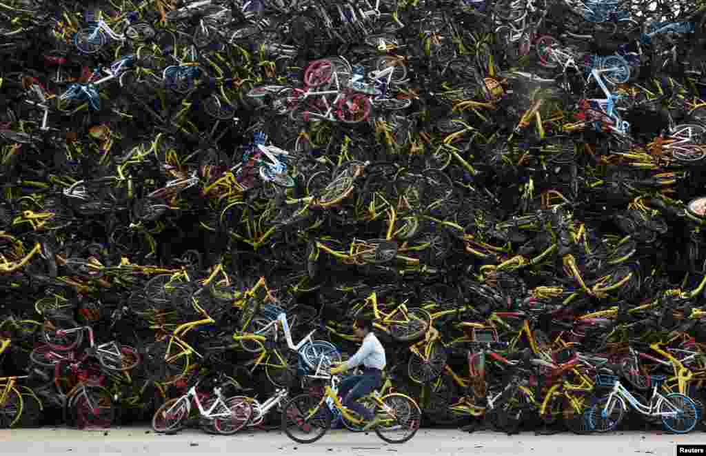 A worker rides a shared bicycle past piled-up shared bikes at a vacant lot in Xiamen, Fujian province, China.
