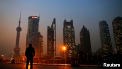 FILE - A man looks at the Pudong financial district of Shanghai.