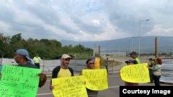 Người dân cầm biểu ngữ phản đối Tổng thống Nicolas Maduro tại biên giới giữa Venezuela với Colombia hôm 8/2/19.