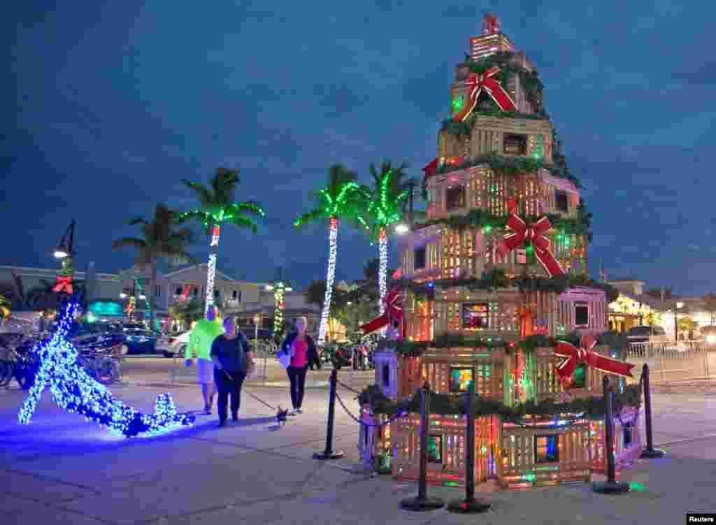People walk past lobster traps stacked in the shape of a Christmas tree at the Historic Seaport in Key West, Florida, U.S., Nov. 29, 2018. (Carol Tedesco/Florida Keys News Bureau/Handout).