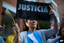 """A woman holds up a sign that reads in Spanish """"Justice"""" as she gathers with others outside the funeral home where a private wake is held for prosecutor Alberto Nisman in Buenos Aires, Jan. 29, 2015."""