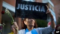 """Một phụ nữ cầm tấm biểu ngữ """"Công Lý"""" khi bà và những người khác tụ họp bên ngoài nhà tang lễ nơi đang diễn ra buổi lễ viếng tang công tố viện Alberto Nisman ở Buenos Aires, Argentina"""