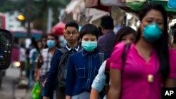 Warga mengenakan masker sebagai perlindungan terhadap merebaknya virus flu babi di Yangon, Myanmar (27/7).