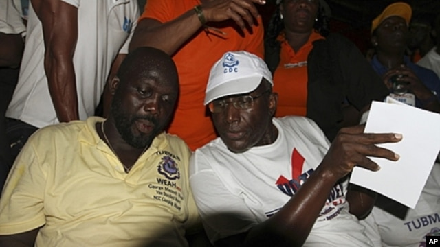 Presidential candidate Winston Tubman (R) sits next to his running-mate George Weah of the Congress for Democratic Change (CDC) during the party's rally at a stadium in Monrovia (file photo)