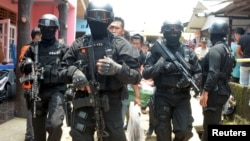 FILE - Armed anti-terror police walk ahead of guard officers in March 2015 after searching the house of a man suspected of being involved in Islamic State-related activities in Indonesia's Banten province.