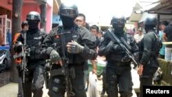 Polisi anti-teror membawa barang bukti dari rumah seorang pria yang diduga terlibat dalam aktivitas terkait ISIS di Tangerang Selatan, Banten (22/3). (Reuters/Antara/Muhammad Iqbal)