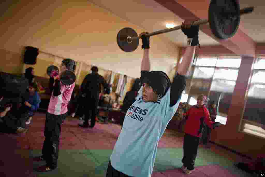 Shabnam Rahimi, 19, (blue) and her sister Sadaf, 18, (pink) lift weights during a practice in a boxing club in Kabul December 28, 2011. Female boxing is especially unusual in Afghanistan, where many girls and women still face a struggle to secure an educa